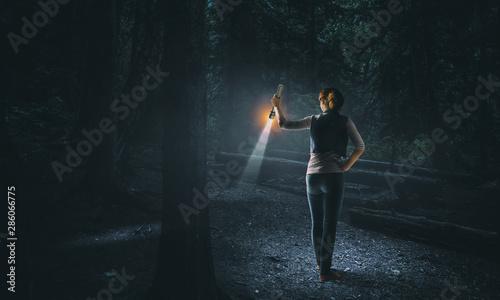 Obraz Young woman holding a flashlight - fototapety do salonu