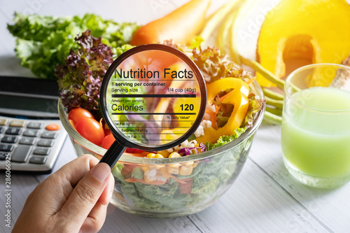 Spoed Fotobehang Eten nutritional information concept. hand use the magnifying glass to zoom in to see the details of the nutrition facts from food , salad bowl