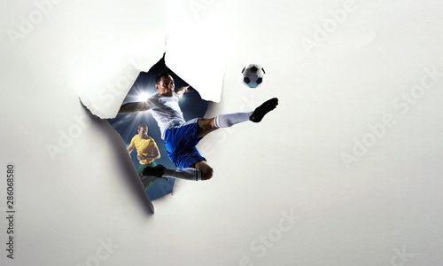 Fotografía  Paper breakthrough hole effect and soccer