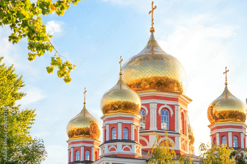 Fototapety, obrazy: Church in the city of Saratov, Russia, Volga region. Attraction, culture, Religion, Christianity, Church of the Protection of the Holy Virgin. Domes of gold color in the summer sunshine