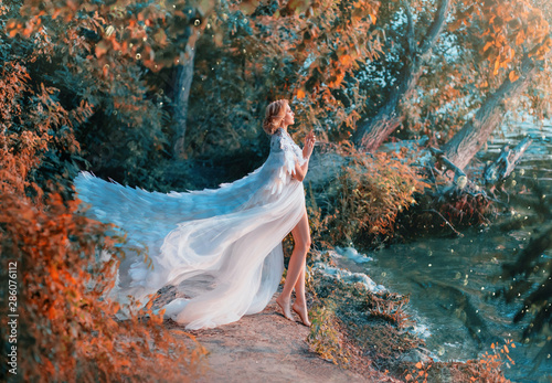 Foto op Canvas Zwaan A woman is standing on the riverbank in a white dress and a raincoat with feathers. Queen of swans. A fashionable cloak for wedding events embroidered with silver and stones flutters in the wind.