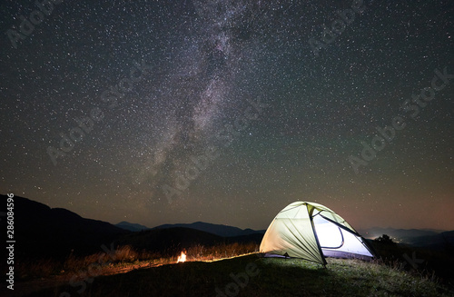 Poster Camping Tourist camping at night in the mountains. Illuminated tent and campfire under wonderful night sky full of stars and Milky way