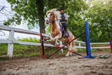 Young playful Caucasian girl with helmet and protective vest on riding adorable pony horse at ranch. Pony skipping obstacle.