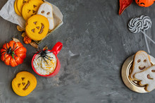 Happy Halloween Background With Copy Space. Red Mug With Traditional Punch, Different Cookies In Shape Of Scary Face, Ghost  And Spider, Pumpkins And Dry Leaves.