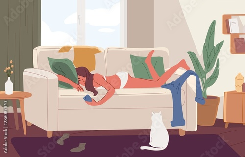 Valokuva Apathetic young woman lying on sofa in messy room or apartment and surfing internet on smartphone
