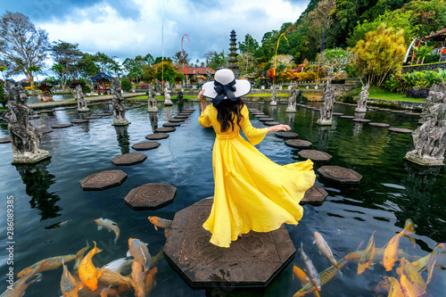 Deurstickers Bali Woman standing in pond with colorful fish at Tirta Gangga Water Palace in Bali, Indonesia.