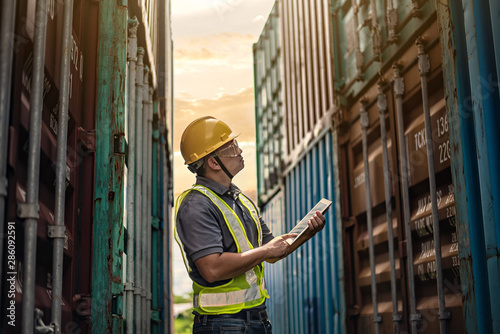 Fényképezés Male engineer, worker inspection checking on container by using tablet