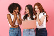 Shocked surprised emotional young three multiethnic girls friends posing isolated over pink wall background using laptop computer.