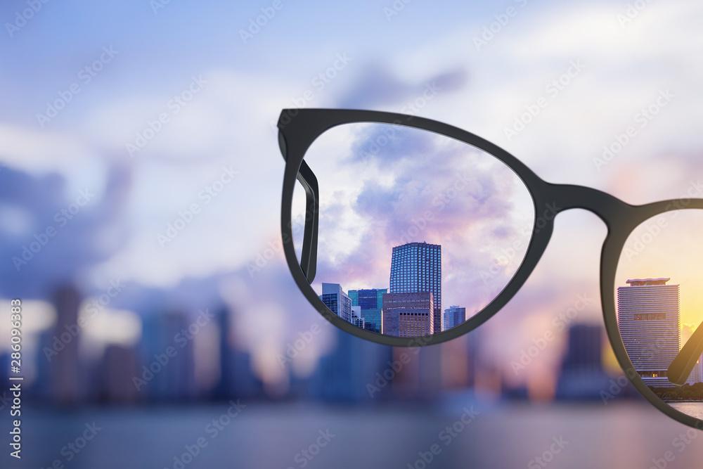 Fototapeta Modern bright city view through eyeglasses