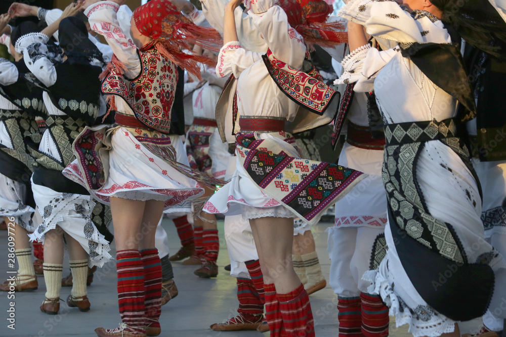 Fototapeta Professional dancers of the Timisul Folklore Ensemble hold hands in a traditional Romanian dance wearing traditional beautiful costumes.
