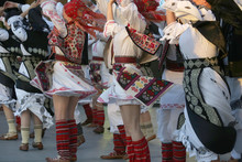 Professional Dancers Of The Timisul Folklore Ensemble Hold Hands In A Traditional Romanian Dance Wearing Traditional Beautiful Costumes.