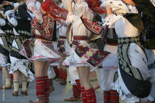 Photo  Professional dancers of the Timisul Folklore Ensemble hold hands in a traditional Romanian dance wearing traditional beautiful costumes