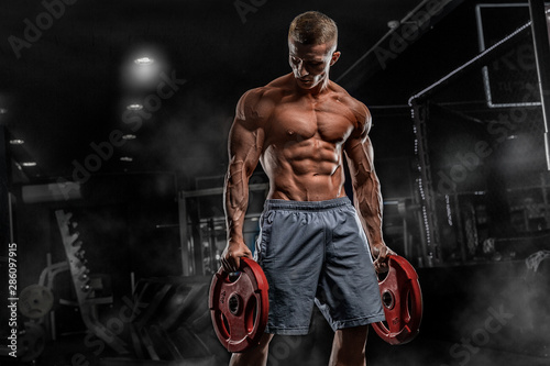 Fotografie, Obraz  Young male athlete bodybuilder posing and doing sports exercises in the gym