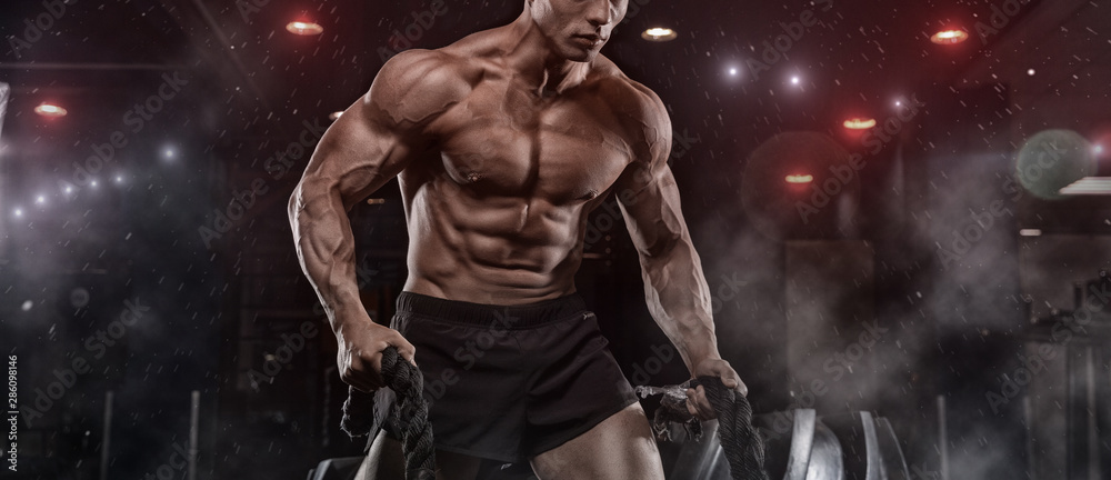 Fototapety, obrazy: Male athlete bodybuilder posing on a black background