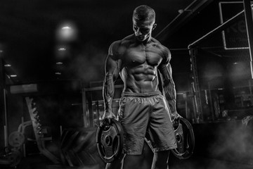 Fototapeta na wymiar Young male athlete bodybuilder posing and doing sports exercises in the gym