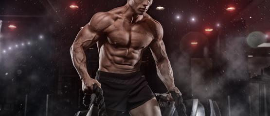 Fototapeta na wymiar Male athlete bodybuilder posing on a black background