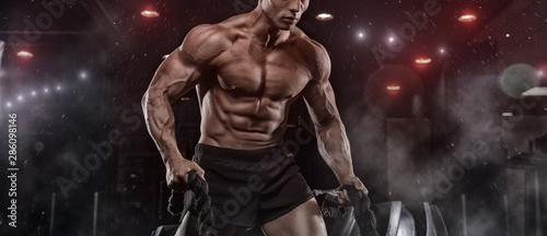 Male athlete bodybuilder posing on a black background Canvas Print