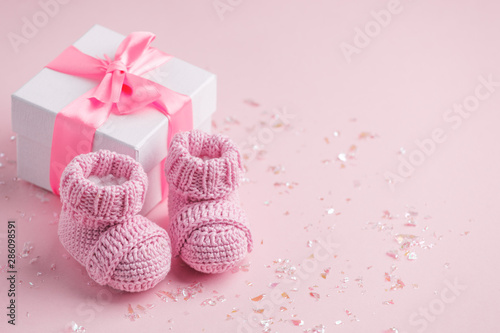 Fotomural Pair of small baby socks and gift box on pink background with copy space for you