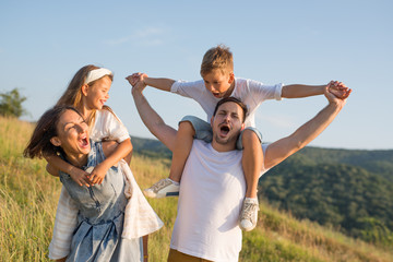 Happy family in nature. Happy family: mother, father, children son and daughter. life is made of little things.