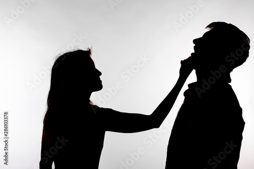 Aggression and abuse concept - man and woman expressing domestic violence in studio silhouette isolated on white background Slika na platnu