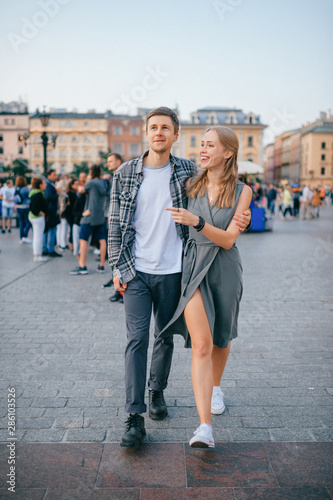 Fototapeta Happy loving couple smiling and walking throug the main square in Krakow (Cracow) obraz