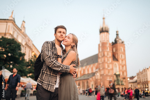 Fototapeta Young loving couple hugs at central square in Krakow (Cracow). obraz
