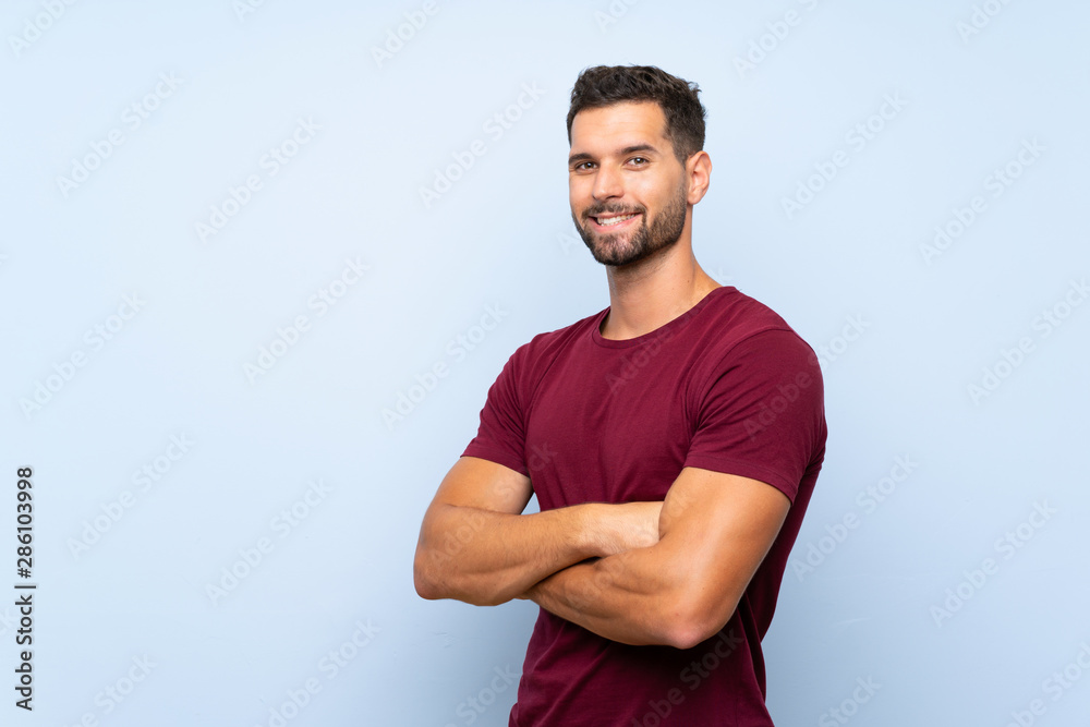 Fototapeta Handsome man over isolated blue background with arms crossed and looking forward