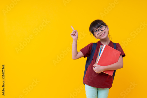Portrait of young Asian girl student holding books pointing up, pretty Thai kid Canvas-taulu