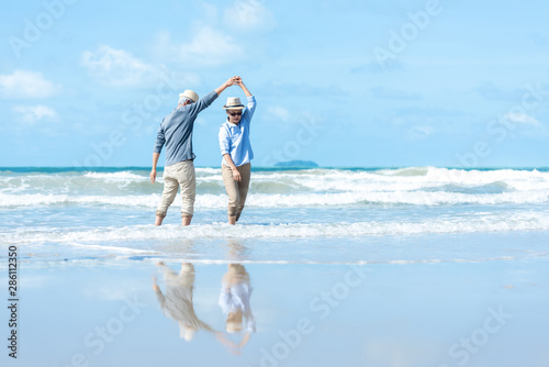 Asian Lifestyle senior couple dancing on the beach happy and relax time. Tourism elderly family travel leisure and activity after retirement in vacations and summer. - 286112350