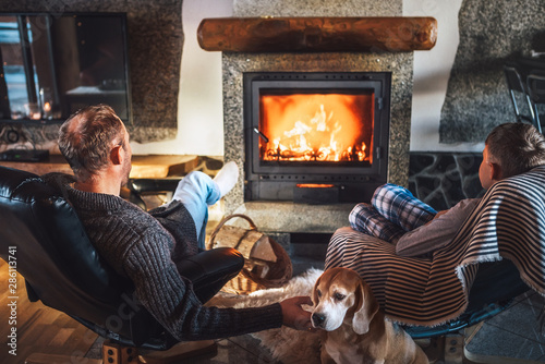 Obraz na plátně Father with son sitting in comfortable armchairs in their cozy country house near fireplace and enjoying a warm atmosphere and flame moves