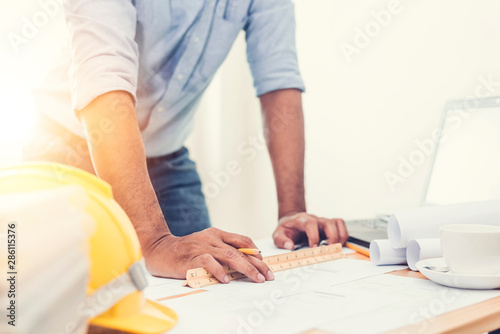 Fototapety, obrazy: Asian architect man Standing working with blueprints sketching a construction project on wood desk at home office.Construction design concept.
