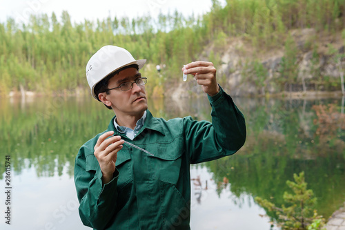 Fototapeta industrial ecologist visually evaluates the response of a water sample from lake