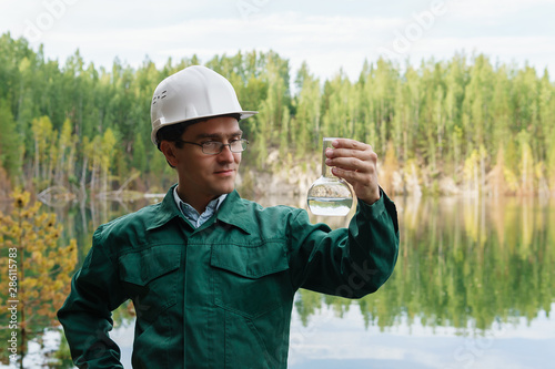 Valokuva  industrial ecologist visually evaluates the response of a water sample from lake