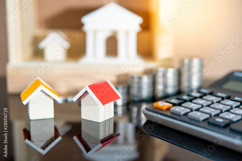 Fototapeta Banking concept. Loan interest rate calculation. Saving money for property investment or real estate development. Home mortgage and lease. Coin stacked, house and bank models with calculator on table. obraz