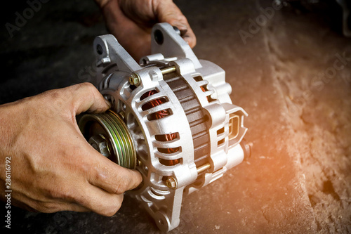 Change new car alternator with hand in the garage or auto repair service center, as background automotive concept Wallpaper Mural