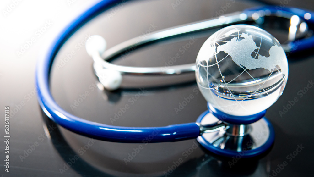 Fototapety, obrazy: Global healthcare concept. World globe crystal glass on blue stethoscope on glossy desk. Health and medical science. Worldwide wellness business