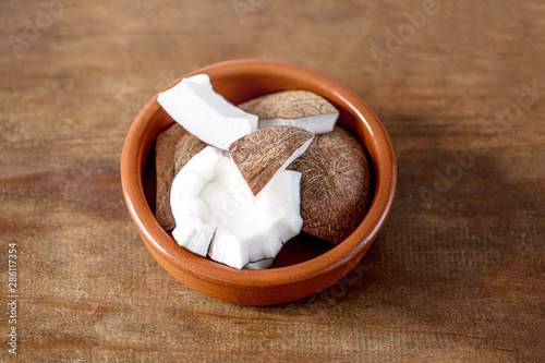 Fotobehang Chocolade Tropical Coconut pieces in a ceramic bowl on wooden background. Coco nut top view. Healthy food concept