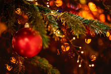 Decorated Christmas Tree On Blurred Background With Golden Sparkling Bokeh Lights And Red Ball. Festive Card