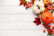 Leinwandbild Motiv Festive autumn decor from pumpkins, berries and leaves on a white  wooden background. Concept of Thanksgiving day or Halloween. Flat lay autumn composition with copy space.