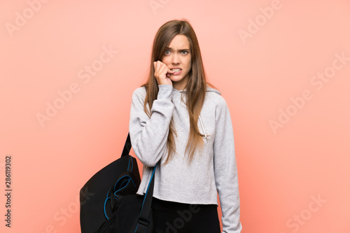 Fotografía  Young sport woman over isolated pink background nervous and scared