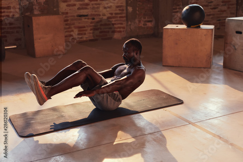Fotomural Sport man doing abs exercise workout at gym indoors. Fitness
