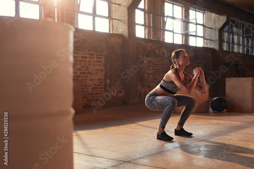 Fotomural Fitness workout. Sport woman doing squat leg exercise at gym