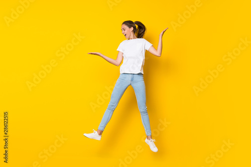 Young woman jumping over isolated yellow wall Tablou Canvas