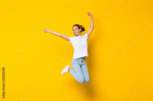 Photo Young woman jumping over isolated yellow wall