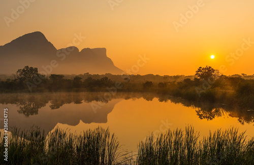 Fotografie, Tablou Landscape of the Hanging Lip or Hanglip mountain peak at sunrise with mist hanging above a swamp lake inside the Entabeni Safari Game Reserve, Limpopo Province, South Africa