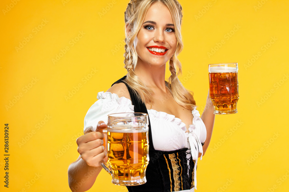 Fototapeta Young sexy Oktoberfest girl waitress, wearing a traditional Bavarian or german dirndl, serving two big beer mugs with drink isolated on yellow background.