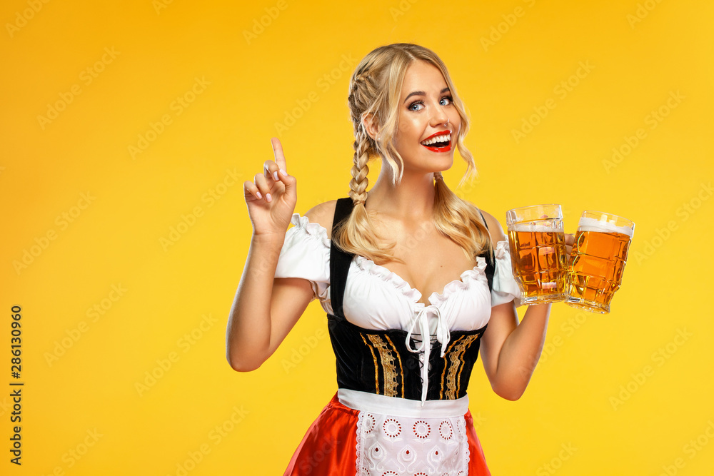 Fototapeta Young sexy Oktoberfest girl waitress, wearing a traditional Bavarian or german dirndl, serving big beer mugs with drink isolated on yellow background. Woman pointing to looking up.