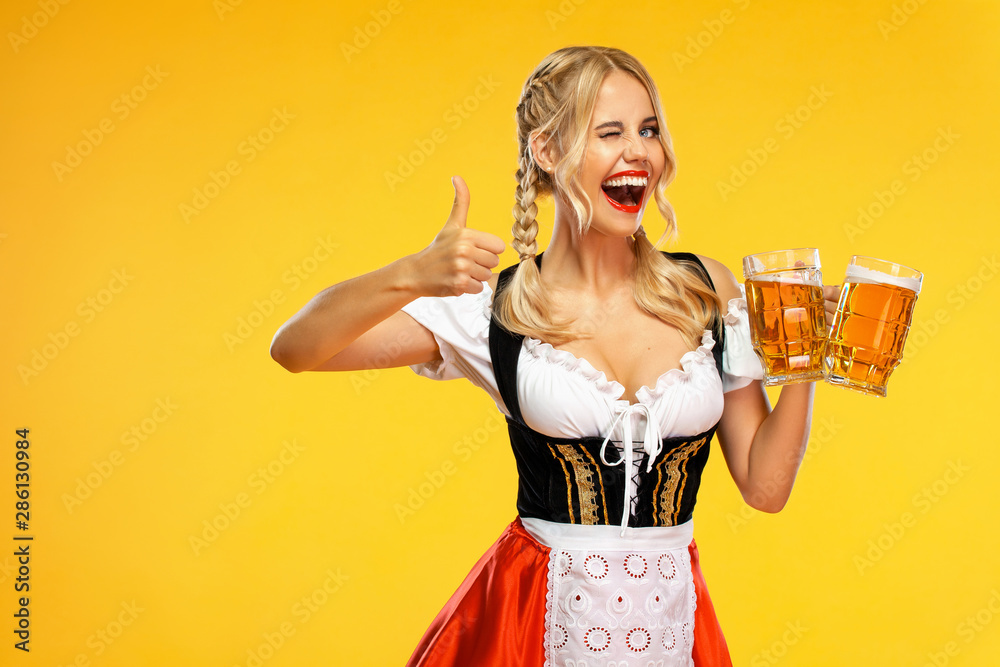 Fototapeta Wow emotion. Young sexy Oktoberfest girl waitress, wearing a traditional Bavarian or german dirndl, serving big beer mugs with drink isolated on yellow background.
