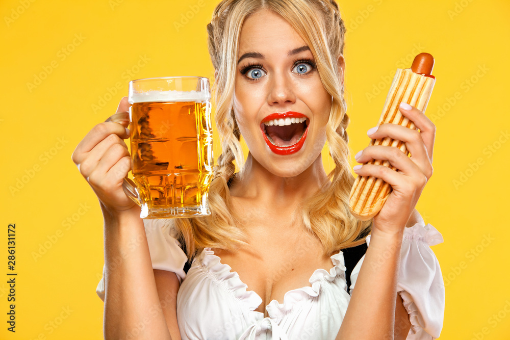 Fototapeta Young sexy Oktoberfest girl waitress, wearing a traditional Bavarian or german dirndl, serving big beer mugs with drink and french hot dog isolated on yellow background.