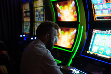 Man Playing A Slot Machine In ...